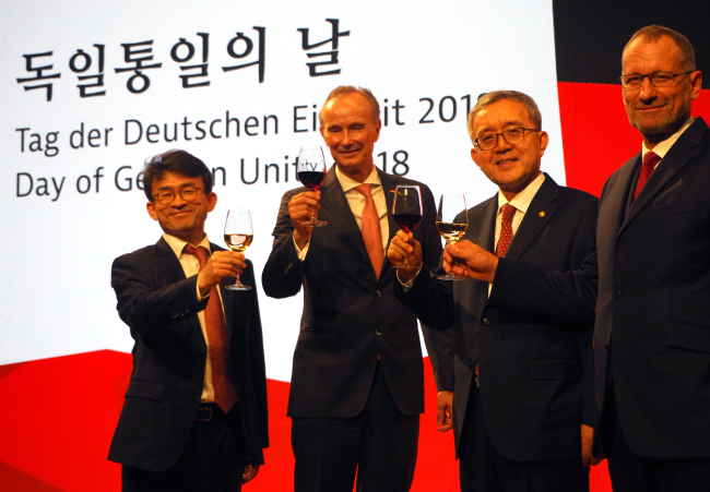 German Ambassador Stephan Auer (second from left), Korean Minister of Personnel Management Kim Pan-suk (second from right), German Trade and Invest CEO Jurgen Friedrich (right) and Standing Commissioner at National Human Rights Commission of Korea Jung Sang-hwan pose at the Day of German Unity reception in Seoul on Friday. (Joel Lee/The Korea Herald)