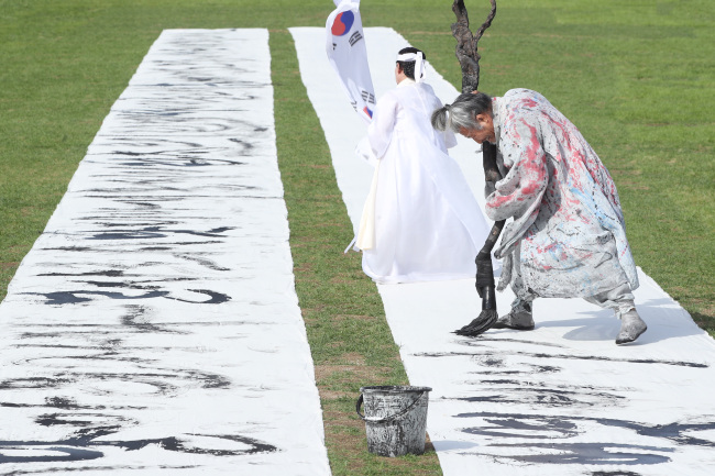 "A 120-meter-long calligraphy writing of the preface for ""Hunminjeongeum,"" a book King Sejong published in 1446 on the Hangeul writing system, is on display at Gwanghwamun Plaza in Seoul on Tuesday. (Yonhap)"