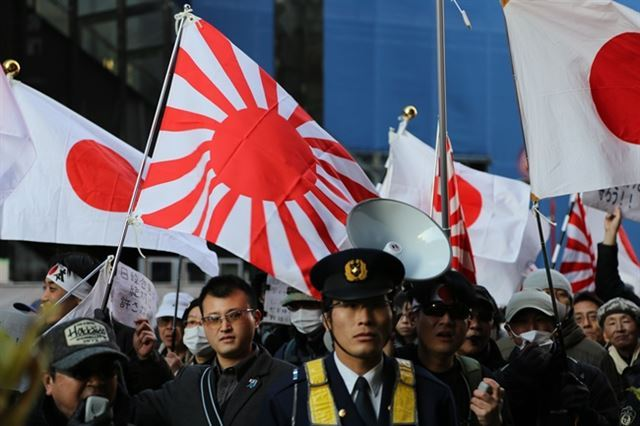 Protestors in Japan fly the Rising Sun flag as they march against the comfort women agreement in January, 2016. (Yonhap)