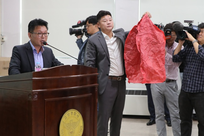 Jang Jong-ick (far left), an officer from the Geyonggi Bukbu Provincial Police agency, speaks during a press conference Tuesday. Another officer is holding a sky lantern that police believes has caused massive fire at an oil storage facility in Goyang, Gyeonggi Province, Sunday. (Yonhap)