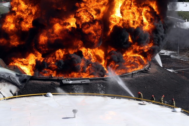 Fire fighters try to extinguish massive fire that erupted at a large oil storage facility in Goyang, Gyeonggi Province, Sunday (Yonhap)