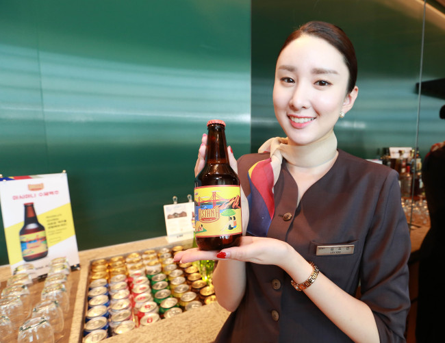 Asiana craft beer is showcased by an Asiana Airlines flight attendant. (Asiana Airlines)