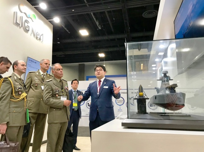 Visitors from the US Army listen to a LIG Nex1 official's presentation of unmanned surface vehicles at the 2018 Annual Meeting & Exposition in Washington on Tuesday. (LIG Nex1)