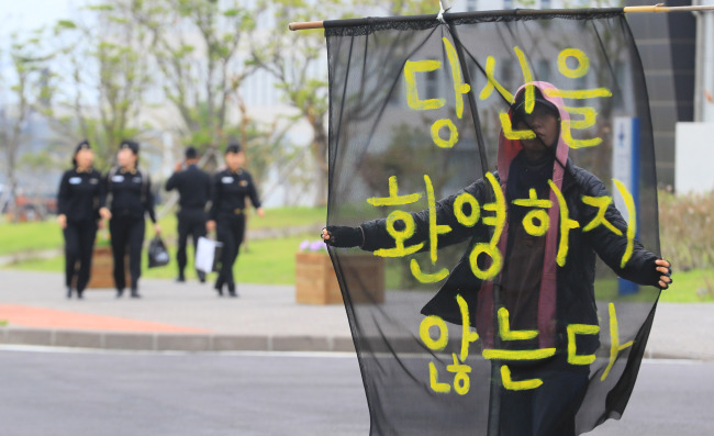An activist stages a protest Tuesday against the International Fleet Review with a sign that reads,