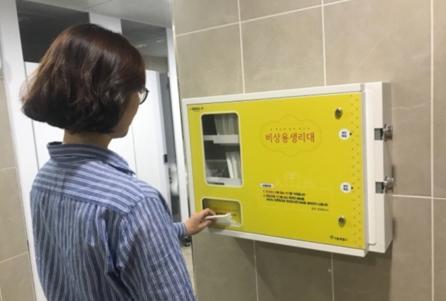 A woman uses a feminine hygiene vending machine that provides free women`s products at a public facility in Seoul. (Seoul Metropolitan Government)