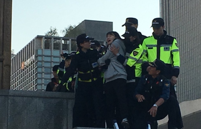 Police remove a protester from the statue of King Sejong in downtown Seoul on Friday. (Twitter user Greg DeRego) 