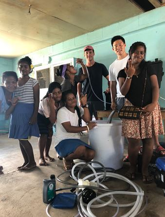 CEO SeYoon Yoon (right, back row) and CFO Will Powers (left, back row), pose for a photograph after installing the Aquifer 360, desalination unit, at Immaculate Hearts College in Kiribati in July. (Bang In-sung)