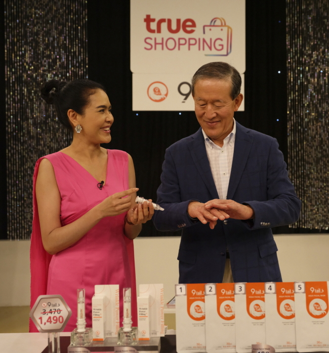 GS Group Chairman Huh Chang-soo (right) tries a product exported by South Korean company 9tails at a studio for True GS, jointly set up by GS Homeshopping, TrueVisions, CP All and Mall Group of Thailand. (GS)