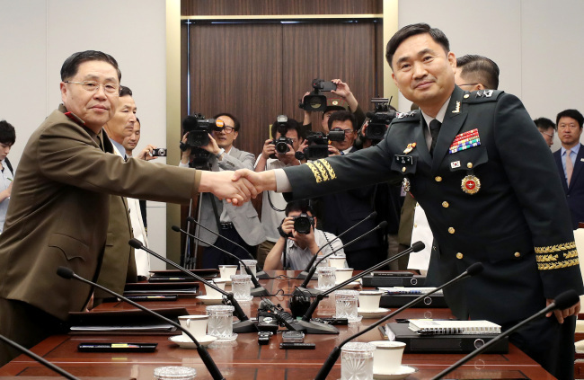 South Korean chief delegate Maj. Gen Kim Do-gyun shakes hands with his North Korean counterpart An Ik-san during a general-level military talks held at Panmunjeom in July. Yonhap