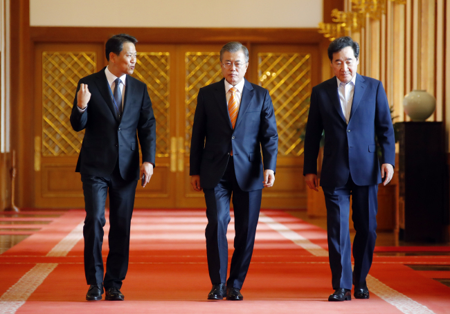 President Moon Jae-in, center, walks into the cabinet meeting on Tuesday. (Yonhap)