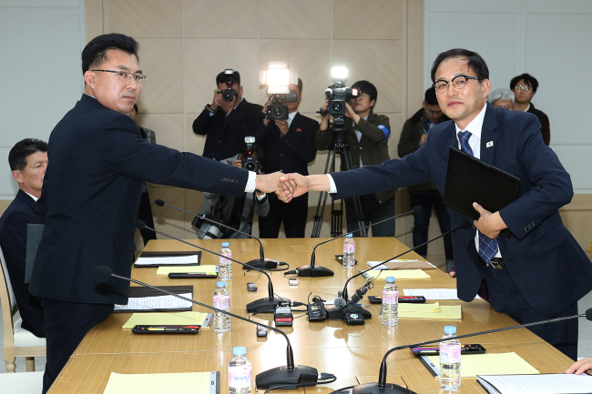 Kim Song-jun, a senior official with the North Korea's Ministry of Environmental Protection, left, shakes hands with Park Chong-ho, deputy chief of the Korea Forest Service at a meeting held in the South-North joint liaison office in Kaesong, North Korea on Monday. (Yonhap)