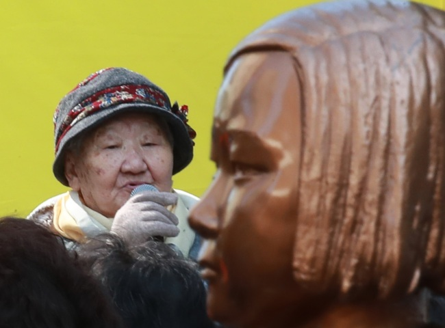 Gil Won-ock, one of the Korean victims of Japan`s wartime sexual slavery during World War II, speaks during a public rally in front of the Japanese Embassy in Seoul on Oct. 17. The statue of a young girl (right), erected in front of the embassy, honors the vicitms. (Yonhap)