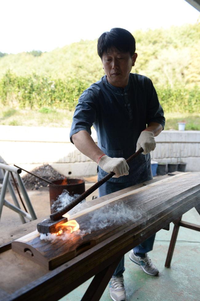 Master craftsman Kim Dong-hwan creates a gayageum at Gayatgo Maeul in Goryeong-gun, South Gyeongsang Province. (GNC21)