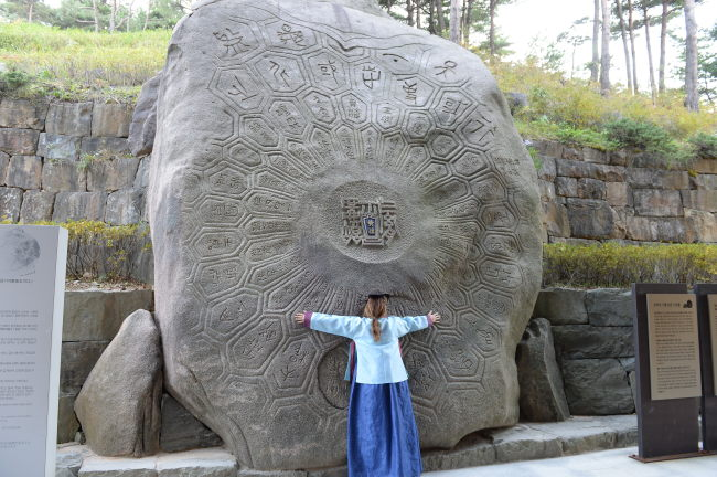 """A person leans into the """"stone mirror"""" at Donguibogam Village. (GNC21)"""