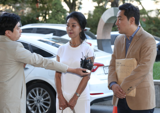 Kang Yong-seok answers a reporter's question as he goes in for police questioning with actress Kim Bu-seon (center) on Oct. 4. (Yonhap)