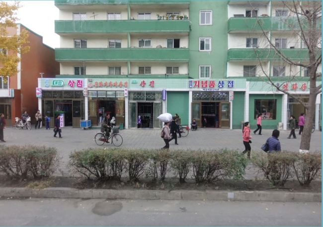 Shops with electric signs lined up on a street in North Korea(Choson Exchange)