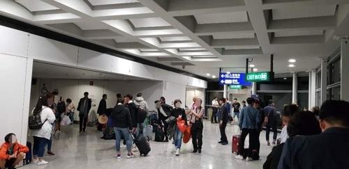 Passengers wait in the hallways at Hong Kong International Airport after a Vietjet flight made an emergency landing on Tuesday, Oct. 30. (Yonhap)