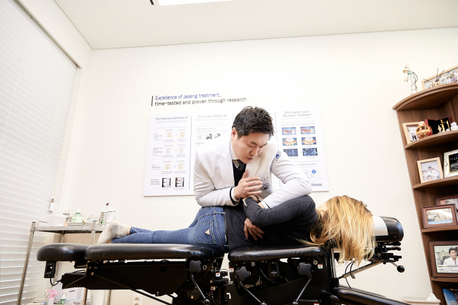 Kim Ha-neul, director of International Medical Center of Jaseng Hospital, practices chuna manipulation to rebalance a foreign patient's musculoskeletal system. (Jaseng Hospital of Korean Medicine)