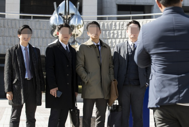 South Korean members of Jehovah`s Witnesses pose for photos in front of the Supreme Court in Seoul on Thursday, after the top court ruled that religious beliefs are to be considered as valid reasons for refusing the country's mandatory military service. (Yonhap)