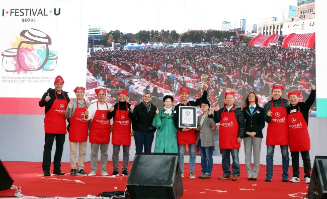 Dimitris Psillakis (seventh from left), chairman of the Mercedes-Benz CSR Committee and CEO of Benz Korea, and official Guinness World Records adjudicator Lucia Sinigagliesi (third from right) pose with participants at a kimchi-making event at Seoul Plaza on Sunday. Guinness acknowledged the event, which involved 3,452 people, as a record-breaker for the most people making kimchi simultaneously. (Mercedes-Benz Korea)