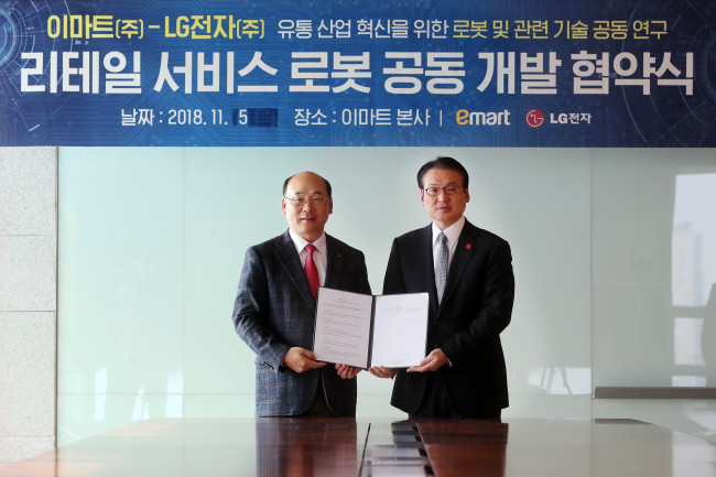 LG Electronics CTO division conversion center Chief Cho Taek-il (left) and E-mart's strategy division Chief Hyung Tae-jun pose for a phot after a signing ceremony held at E-mart headquarters on Monday. (E-mart)