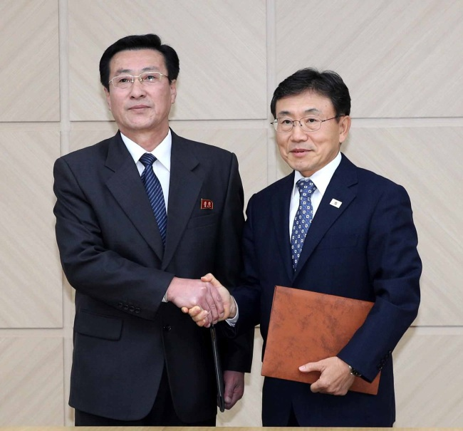 Kwon Deok-cheol (right), South Korea's Vice Health Minister, and his North Korean counterpart, Park Myong-su, pose for a photo after reaching an agreement during an inter-Korean meeting held in the North's border town of Kaesong, Wednesday. (Yonhap)
