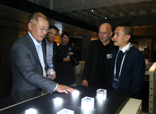 """Hyundai Motor Chief Vice Chairman Chung Eui-sun (first left) is introduced to Ou Jifei's artwork at the opening ceremony of Hyundai's media art project simultaneously underway in Seoul, Beijing and Moscow, """"Future Humanity -- Our Shared Planet,"""" at Hyundai Motor Studio Beijing on Thursday. (Hyundai Motor)"""