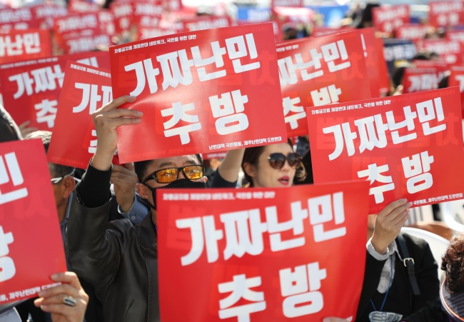 Korean participants attend a anti-refugee rally and hold a sign that says