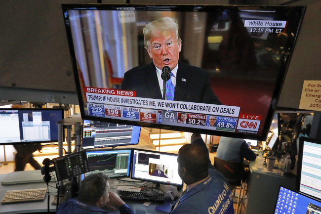 A screen at the New York Stock Exchange shows US President Donald Trump at a press conference. (AP-Yonhap)