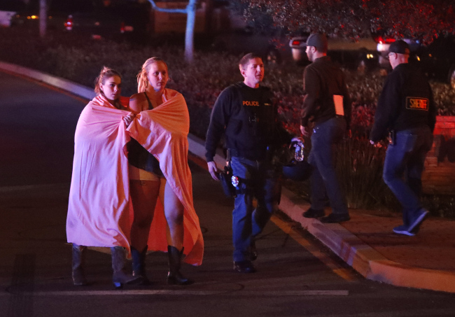 Two women wearing blankets leave the area near the Borderline Bar and Grill in Thousand Oaks, California, USA, Thursday, where 12 people were killed. A sheriff's deputy, 10 attendees and the gunmen were killed. (EPA-Yonhap)