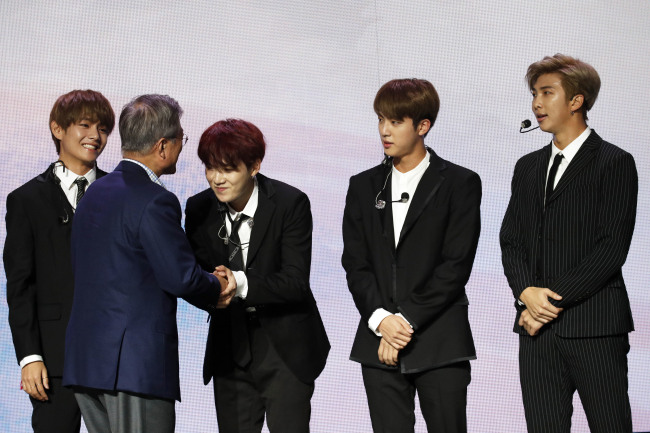 The bandmates of BTS shake hands with President Moon Jae-in during a Korean cultural event in Paris, on Oct. 14. (AP-Yonhap)