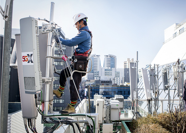 An engineer of SKT works on the installation of a 5G antenna unit on the rooftop of a building in Myeong-dong, central Seoul, Wednesday. (SK Telecom)