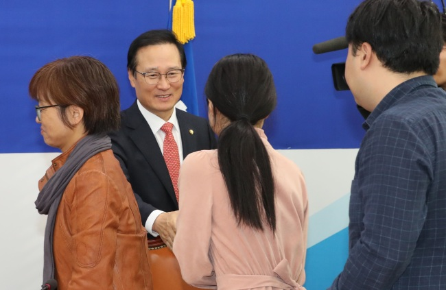 Rep. Hong Young-pyo (second from right) shakes hands with youth activists on Wednesday. (Yonhap)