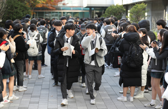 Third-year students leave the school gate as their juniors and teachers cheer for them, a day before Suneung, or the national college entrance exam, at Seocho High School in Seoul on Wednesday. (Yonhap)