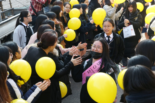 Seniors leave the school gate as other students and teachers cheer them on, a day before Suneung at Seolwol Girls' High School in Gwangju, Wednesday. (Yonhap)