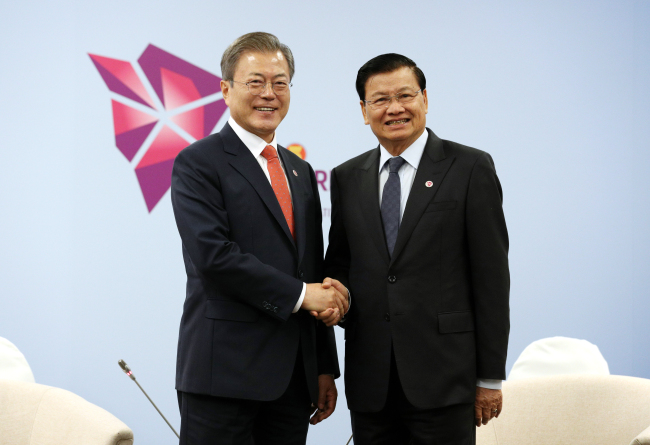 President Moon Jae-in and Prime Minister of Laos Thongloun Sisoulith shake hands ahead of their meeting in Singapore on Wednesday. Yonhap