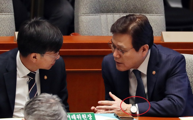 Choi Jong-ku, chairman of the Financial Services Commission (right), is seen wearing a fake high-end watch (circled in red) at the National Assembly in Seoul. (Yonhap)