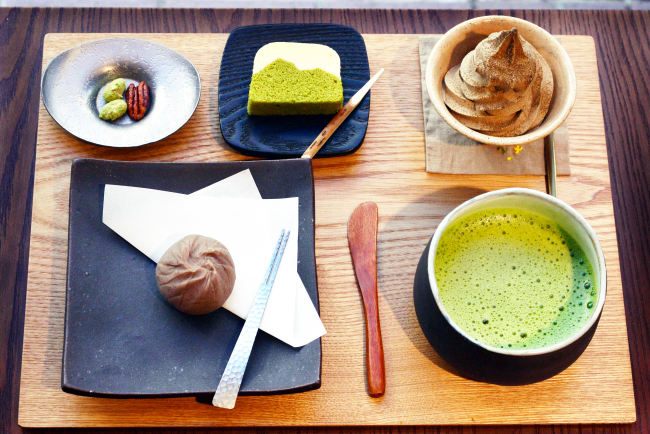 Mochibang serves treats like chestnut ohagi (front, left), which features a marron glace coated in bean paste infused with marron glace syrup; creamy swirls of hojicha ice cream topped with powdered hojicha (back, right); and a steamed bean paste cake called ukishima (back, center). Treats can be paired with frothy bowls of matcha (front, right) or enjoyed with tidbits like candied nuts (back, left). (Photo credit: Park Hyun-koo/The Korea Herald)