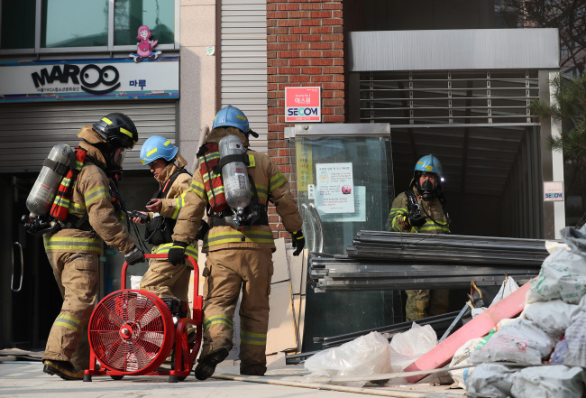 Firefighters enter the YWCA building to check on remaining flames. (Yonhap)