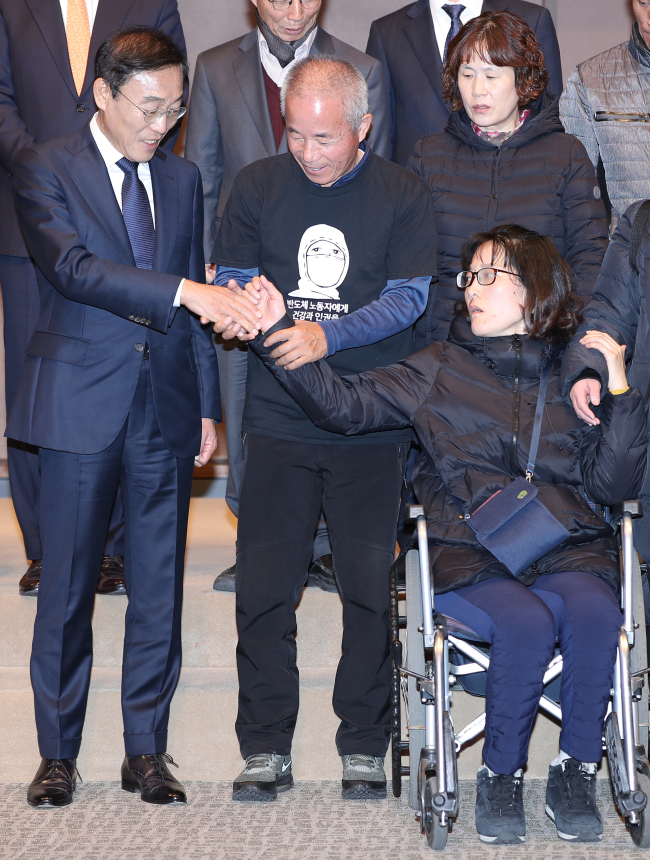 Samsung CEO Kim Ki-nam (left) holds hands with Han Hye-kyung (right), a former Samsung worker who is suffering a brain illness, at the press conference on Friday. (Yonhap)