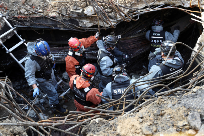 Police and fire authorities survey the KT site in Ahyeon-dong, Seoul, where the fire broke out on Saturday, causing massive network damage there and in neighboring regions. Yonhap