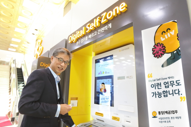 "KB Kookmin Bank CEO Hur Yin demonstrates the ""smart teller machine"" at KB's Yeouido branch in August 2018. The machine connects customers to bank employees via video chat, enabling them to complete banking tasks that previously required a physical visit to the bank. Examples include applying for credit cards and creating new accounts. (KB Kookmin Bank)"