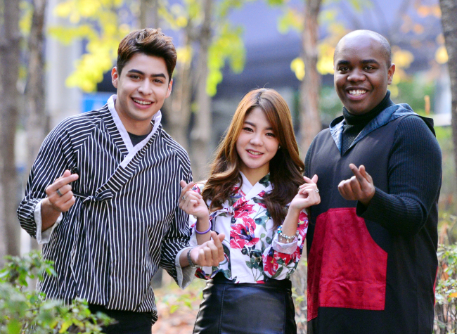 "Members of the project performance team Hangeul make ""finger heart"" gestures at a park in the Seocho district of Seoul on Nov. 16. From left: Christian Burgos, Saori Fujimoto and Terris Brown. (Park Hyun-koo/The Korea Herald)"