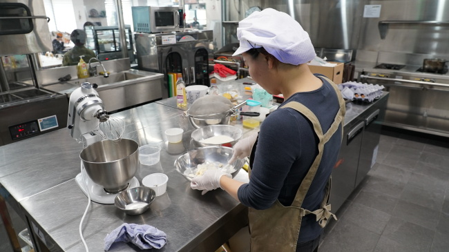 A WeCook tenant prepares food in the shared kitchen. (Lee So-jeong / The Korea Herald)