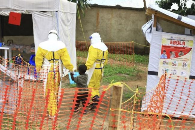 In this file photo dated Sunday, Sept. 9, 2018, health workers walk with a boy suspected as having the Ebola virus at an Ebola treatment centre in Beni, Eastern Congo. According to a WHO announcement Thursday Nov. 29, 2018, Congo's deadly Ebola outbreak is now the second largest in history, and predicted the outbreak will last at least another six months before it can be contained. (AP)