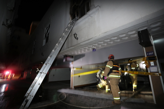 Firefighters on Sunday conduct an on-site investigation of an unmanned motel in Yeosu, South Jeolla Province, where two people were killed in a fire. (Yonhap)