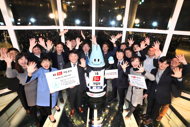 KT and Lotte World Tower officials celebrate the launch of 5G on robot Lota at the tower on Saturday. (KT)