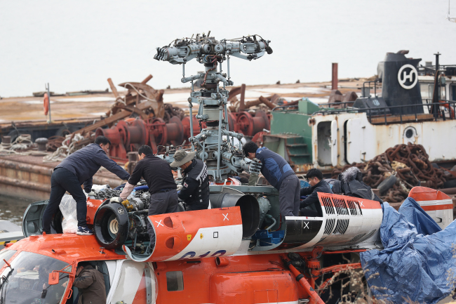 Authorities dismantle a helicopter after retrieving from the Han River near Gangdong Bridge on Sunday. (Yonhap)
