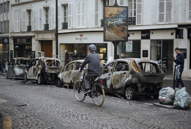 A man rides his bicycle past by charred cars, near the Arc de Triomphe, in Paris, Sunday, Dec. 2, 2018. A protest against rising taxes and the high cost of living turned into a riot in the French capital Saturday, as activists caused widespread damage and tagged the Arc de Triomphe with multi-colored graffiti during clashes with police. (AP)