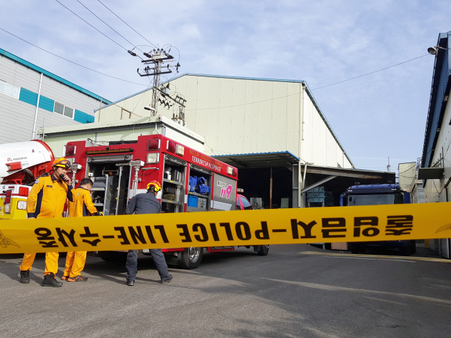 This photo, taken on Wednesday, shows fire fighters dealing with a toxic gas leak at a waste water treatment plant in the southern port city of Busan. (Yonhap)